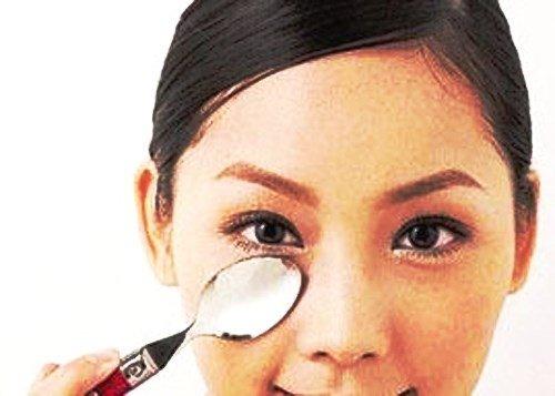 Девушка прикладывает холодную ложку к мешкам под глазами
