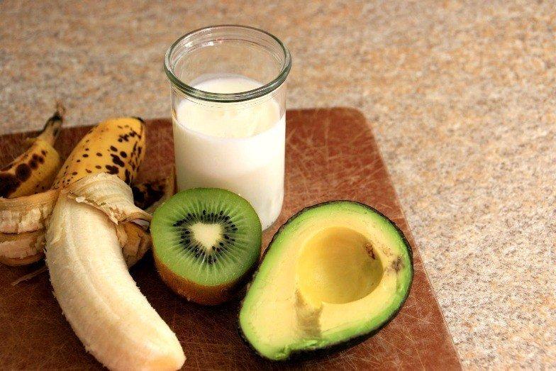 Авокадо, киви, банан и молоко на столе