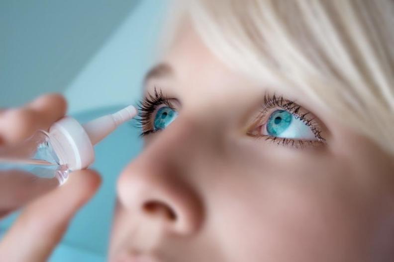 Девушка использует капли для глаз