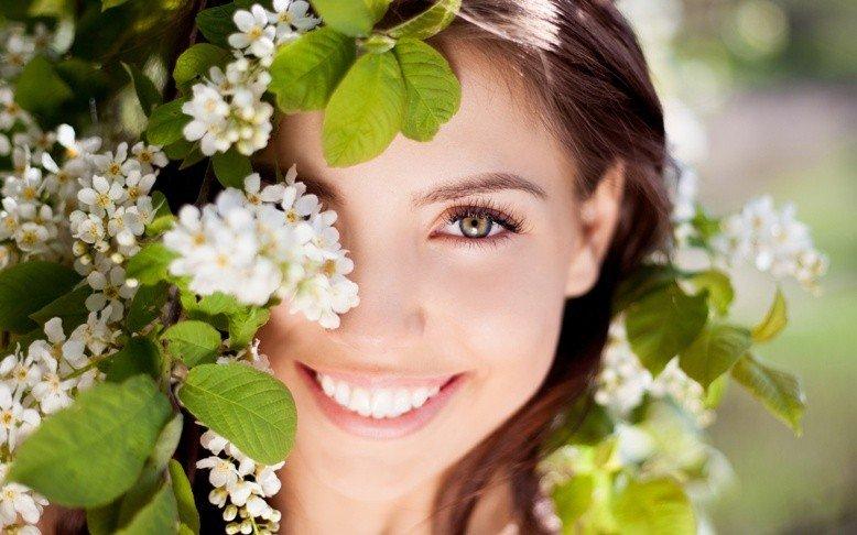 Девушка со свежей кожей лица и век и цветущие ветви дерева