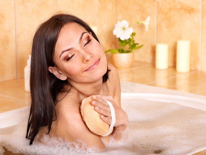 Девушка в ванной с мочалкой