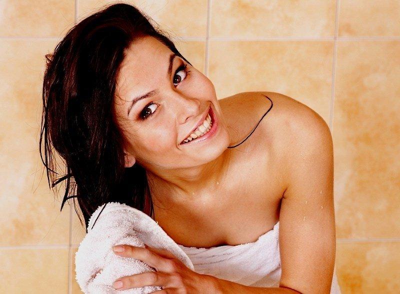 Смывка волос в домашних условиях, девушка с полотенцем вытирает волосы