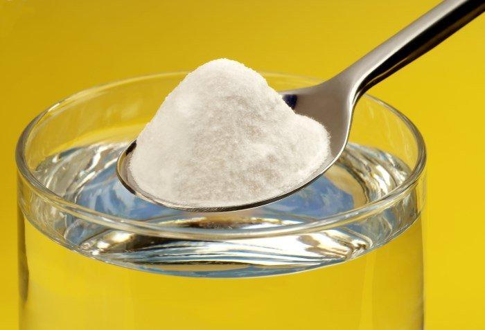 Пищевая сода в ложке и вода
