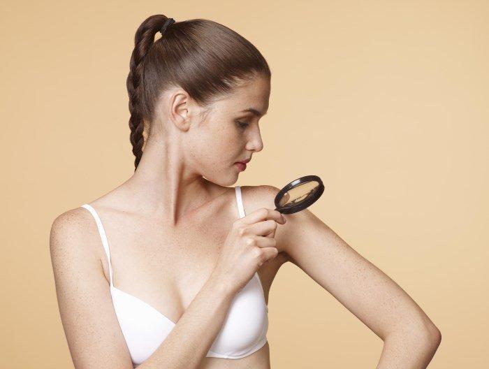 Девушка осматривает кожу