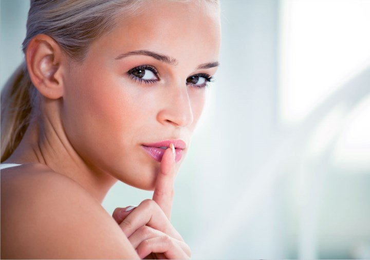 Девушка пальцем касается губ