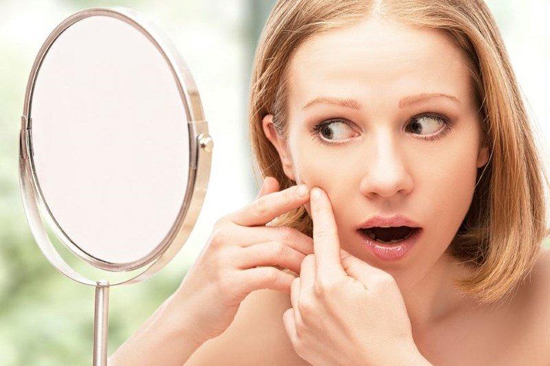 Проблемная кожа лица, девушка смотрится в зеркало