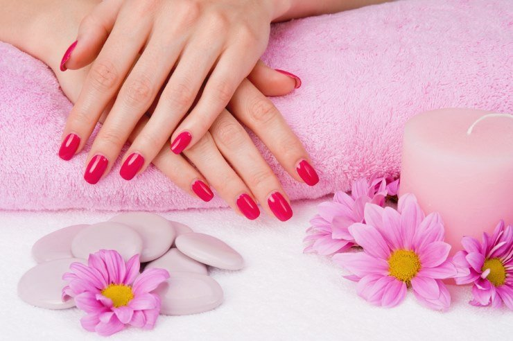 Женские руки, свеча, полотенце, цветы, камешки