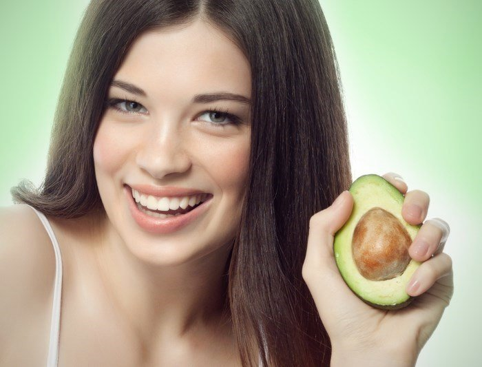 Девушка с густыми волосами и авокадо в руке