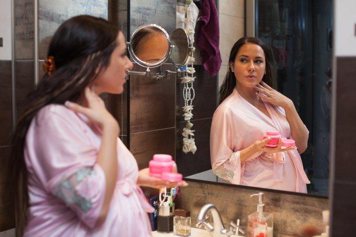 Молодая беременная женщина перед зеркалом