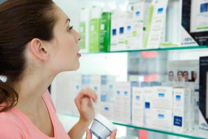 Девушка выбирает косметику в аптеке