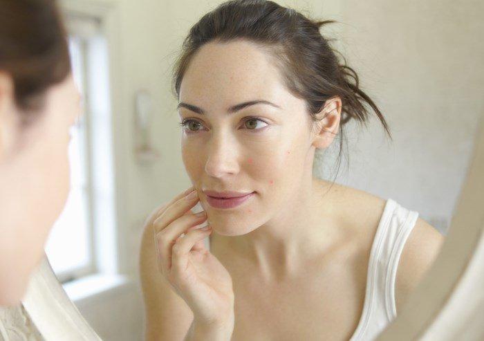 Женщина рассматривает лицо в перед зеркалом