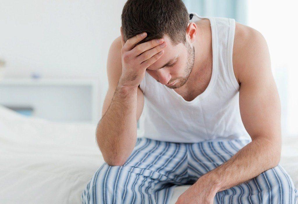 Мужчина задумался сидя на кровати