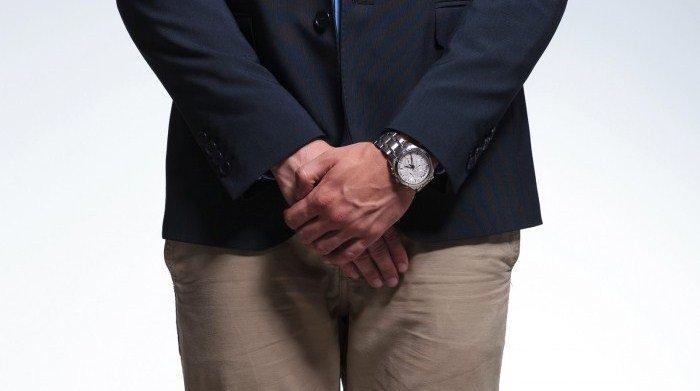Мужчина держит руки в области паха