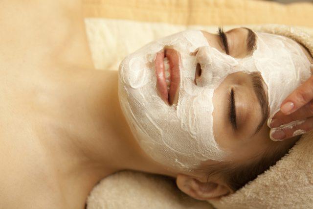 Девушке наносят белую глину на лицо