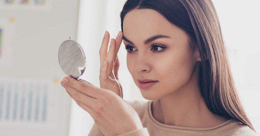 Девушка смотрит в зеркальце на свои брови